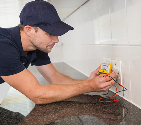 Electrician working at plug socket in a kitchen
