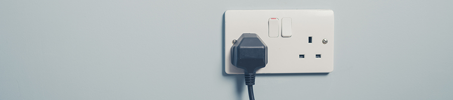 Uk Wall Socket And Cord On Blue Wall